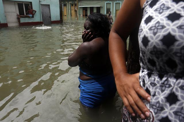 Algunas mujeres en el exterior de sus viviendas inundadas en un barrio de La Habana, por la penetración del mar que ocasionó el paso por Cuba del huracán Irma, el 9 de septiembre. El evento climático se sumó al enfriamiento de las relaciones con Estados Unidos, como un factor que perjudicó la alicaída economía del país. Crédito: Jorge Luis Baños/IPS