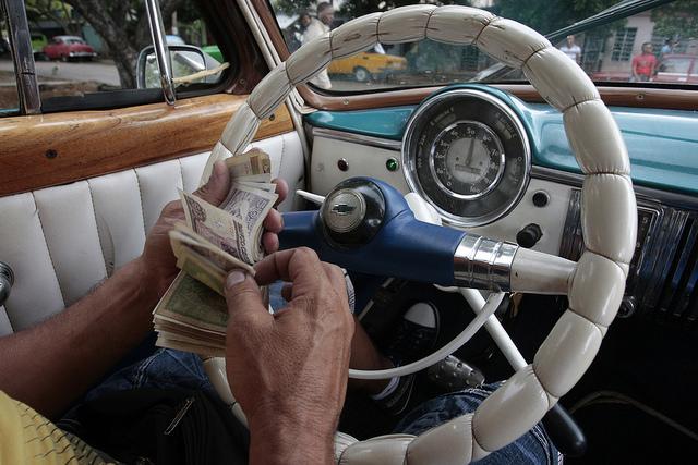 El conductor de un taxi privado de La Habana sostiene un fajo de billetes de los dos tipos de moneda que conviven en Cuba, en busca de dar el vuelto a un cliente por su pago. Crédito: Jorge Luis Baños/IPS