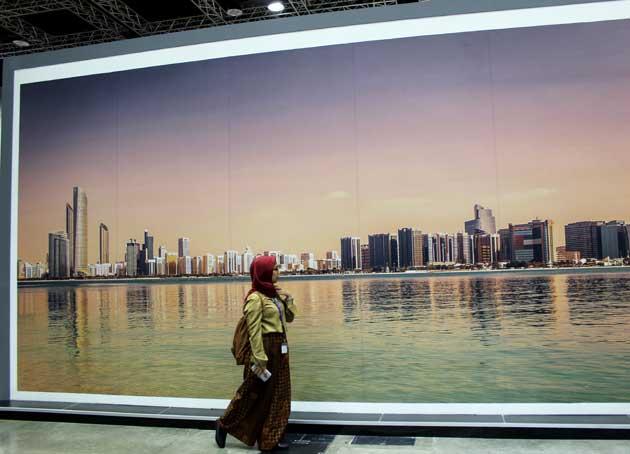 Una participante de Malasia del Foro Urbano Mundial pasa frente al stand de Abu Dhabi, organizador del próximo foro en 2020, cuando se revisará el avance en la seguridad de las mujeres. Crédito: Manipadma Jena/IPS.