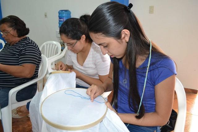 Artesanas de distintas edades de la Cooperativa Multiactiva de Producción Artesanal de Ao Po´i, mientras bordan las delicadas telas de algodón en sus bastidores. Crédito: Ingrid Zabaleta/FAO