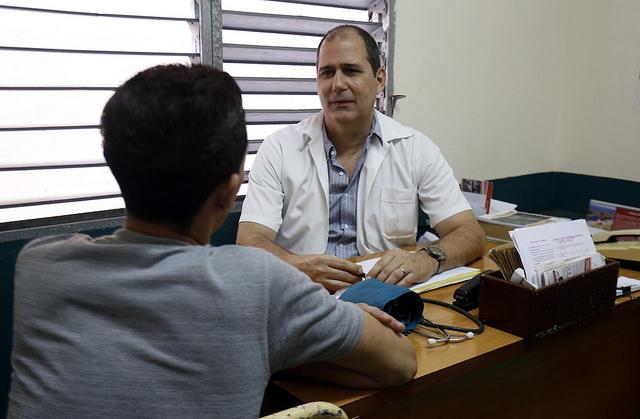 El médico Danilo Machado con Gilberto Pérez, uno de los cinco pacientes seropositivos que atiende en su consultorio en La Habana, donde tiene a su cuidado a 994 personas. La atención en consultorios de medicina familiar a las personas con VIH es parte de la estrategia de Cuba. Crédito: Jorge Luis Baños/IPS