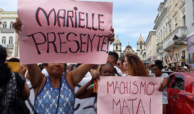 Dos mujeres afrodescendientes, para quienes Marielle Franco era un referente, levantan carteles contra su asesinato en la plaza Terreiro de Jesús, en la ciudad brasileña de Bahia. Muchos otros con similar espíritu de reivindicación y de exigencia de justicia y no impunidad abundaron durante la manifestación de la Asamblea Mundial de Mujeres. Crédito: Mariela Jara/IPS