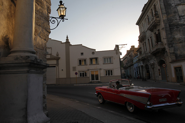 Un automóvil clásico de la marca estadounidense Chevrolet, modelo Bel-Air convertible de 1957, empleado por conductores privados para realizar paseos turísticos transita en busca de clientes por una céntrica calle del casco histórico de La Habana Vieja en Cuba, ahora que el boom de visitas de ciudadanos del país vecino ha caído. Crédito: Jorge Luis Baños/IPS