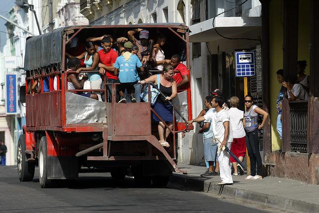 Pasajeros descienden de un camión de propiedad privada que presta servicio de transporte, en la oriental provincia de Santiago de Cuba. Crédito: Jorge Luis Baños/IPS