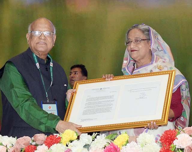 Ministro de Finanzas de Bangladesh, AMA Muhith, entrega una réplica de la carta de la ONU en reconocimiento a la graduación de Bangladesh como país en desarrollo a la primera ministra Sheikh Hasina Wazed, en una recepción organizada en su honor en la capital del país. Crédito: PID (Departamento de Infrmación a la Prensa.