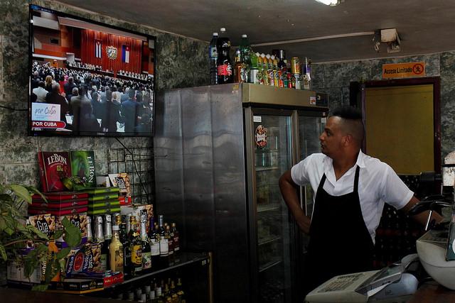 El empleado de una cafetería estatal en La Habana observa la transmisión en vivo de la sesión de La Asamblea Nacional del Poder Popular (parlamento) en que se eligió al nuevo presidente, vicepresidentes y otros miembros del Consejo de Estado, máximo órgano ejecutivo de Cuba. Crédito: Jorge Luis Baños/IPS
