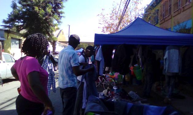 En la feria dominical, gana espacio la venta de ropa y de zapatos usados, que los asistentes se prueban en la calle transformada en un centro social al aire libre para la comunidad haitiana que vive en Estación Central, un municipio popular del oeste de Santiago de Chile, cerca del centro de la ciudad. Crédito: Orlando Milesi/IPS