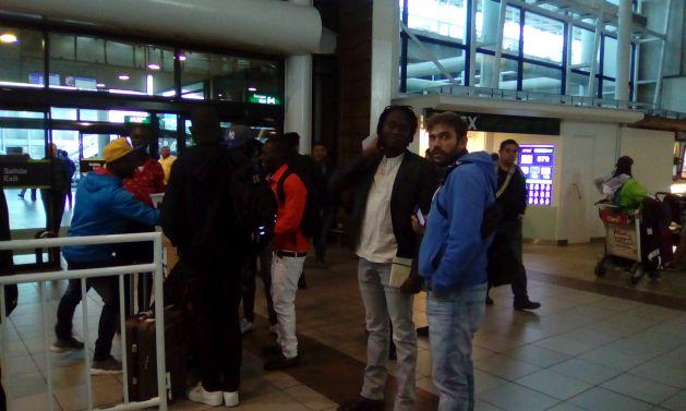 Un grupo de haitianos recién llegados en un vuelo procedente de Panamá, escala habitual desde Puerto Príncipe, dialogan con familiares y amigos que han venido a recibirlos, en el terminal del Aeropuerto Internacional de Pudahuel en Santiago. Crédito: Orlando Milesi/IPS