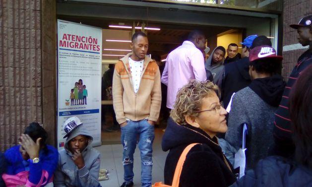Un grupo de haitianos conversan y se ayudan entre ellos, mientras esperan para realizar trámites en una de las largas filas que se forman todos los días laborales desde las cuatro de la madrugada a las puertas de una oficina migratoria al lado de una de las principales arterias de Santiago y a solo tres cuadras del palacio de la Moneda, sede del gobierno. Crédito: Orlando Milesi/IPS