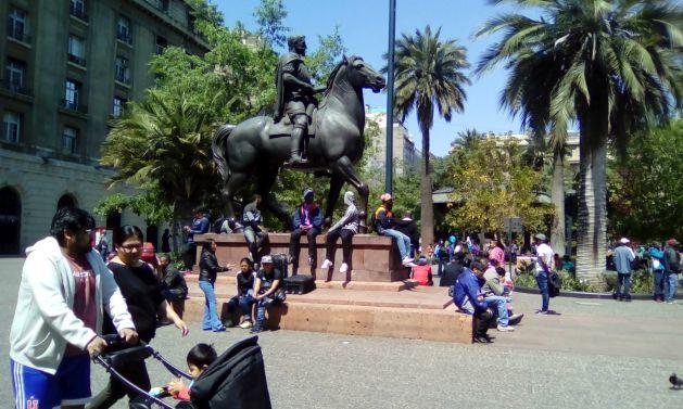 La Plaza de Armas, en el corazón de Santiago, es un habitual punto de encuentro de los inmigrantes en la capital. Siguen predominando los de origen peruano, la mayor población migrante de Chile, pero ya son reconocibles grupos de haitianos que se congregan también en el lugar. Crédito: Orlando Milesi/IPS