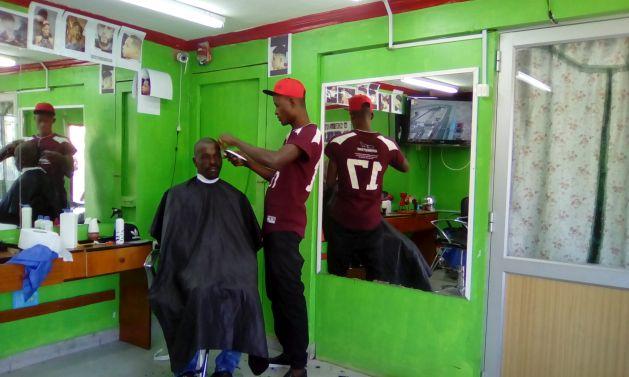 En la calle Pingüinos, en el popular municipio de Estación Central, uno de los dos que congrega un mayor número de migrantes de Haití en Santiago de Chile, un peluquero procedente del país caribeño ha establecido una barbería donde se habla en creole y se atiende a los connacionales. Crédito: Orlando Milesi/IPS