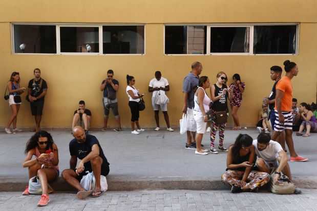 Numerosas personas acceden a Internet a través de puntos de conexión inalámbrica (wifi), en el casco histórico de La Habana Vieja. La estatal Empresa de Telecomunicaciones de Cuba, única en el sector, abrió en julio de 2015 las 35 primeras zonas de navegación en Internet con tecnología wifi en sitios públicos y abiertos como parques. Ampliar paulatinamente el acceso a Internet, telefonía móvil y correo electrónico, fue parte de la agenda de Raúl Castro, pero los avances son insuficientes. Crédito: Jorge Luis Baños/IPS