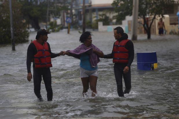 Miembros de la Defensa Civil brindan asistencia a una mujer durante las inundaciones costeras ocasionadas por el huracán Irma, en el céntrico barrio de Vedado, en La Habana, en septiembre de 2017. La severidad de eventos climáticos como Irma y evidencias científicas acumuladas, llevó a Cuba a aprobar en abril de ese año el Plan de Estado para el enfrentamiento al cambio climático, conocido como Tarea Vida, para lograr la adaptación del país insular caribeño. Crédito: Jorge Luis Baños/IPS