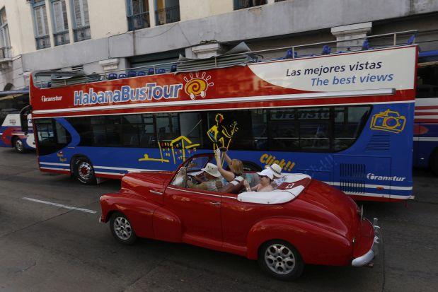 Turistas extranjeros toman fotos desde un automóvil clásico, gestionado por un conductor privado, en el centro histórico de La Habana. Desde 2015, Cuba vive un boom turístico sin precedentes, que cerró en 2017 con la cifra récord de 4,7 millones de visitantes internacionales y aspira a captar en 2018 cinco millones de turistas de otros países. Crédito: Jorge Luis Baños/IPS