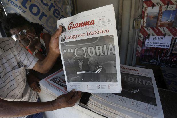 """Un hombre muestra la portada de una edición especial del periódico oficial Granma, conmemorativa por el VII Congreso del Partido Comunista de Cuba, el único legal del país y que aprobó, en abril de 2011, el programa de las transformaciones económicas y sociales encauzadas por el gobierno de Raúl Castro. El plan, titulado """"Lineamientos de la Política Económica y Social"""", fue revisado en abril de 2016. Crédito: Jorge Luis Baños/IPS"""