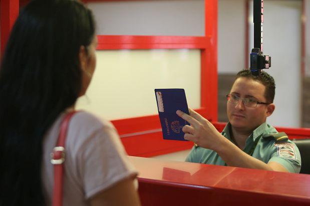 Un funcionario chequea el pasaporte de una ciudadana cubana antes de la salida de un vuelo, en el Aeropuerto Internacional José Martí, en La Habana. Cuba revisó su política migratoria en un proceso que comenzó con la entrada en vigor, en enero de 2013, de un decreto que eliminó engorrosos trámites que dificultaban las posibilidades de viajar a los residentes en este país caribeño. Crédito: Jorge Luis Baños/IPS