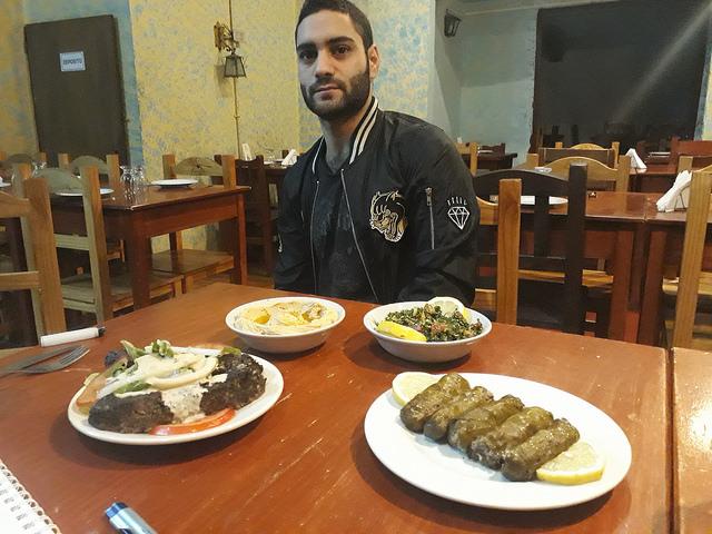 Fares al Badwan, quien llegó a Argentina en 2011, cuando apenas se iniciaba el sangriento conflicto en Siria, muestra algunas de las delicias árabes que se preparan en el restaurante familiar, entre ellas los tradicionales hummus y tabule. Crédito: Daniel Gutman/IPS