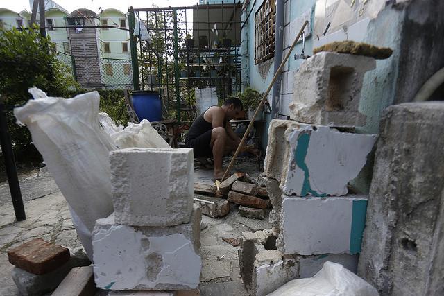 Un vecino del municipio capitalino de Plaza de La Revolución, rodeado de materiales reciclados de construcción, repara la instalación hidráulica de su vivienda, en La Habana, en Cuba. Crédito: Jorge Luis Baños/IPS