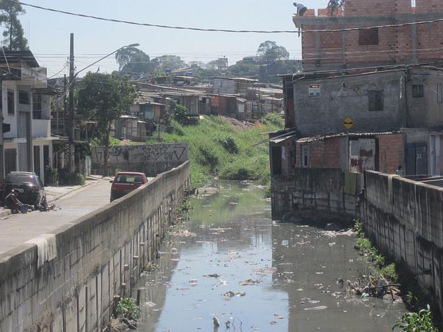 Los asentamientos urbanos en la periferia se hunden en la precariedad y carecen de saneamiento básico, como este de Capão Redondo, en el extremo sur de São Paulo. En un lado un asentamiento ya consolidado de construcciones de ladrillo sin pintura de dos o tres pisos, del otro una ocupación improvisada de 800 familias que reclaman tierra para construir sus viviendas, y en medio un riachuelo contaminado y sedimentado que escurre hacia un manantial que abastece la metrópoli brasileña. Crédito: Mario Osava/IPS