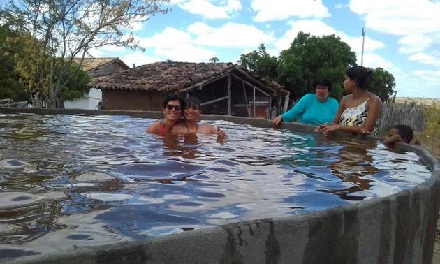 Familiares de José Antonio Borges se divierten en el estanque de hierro-cemento de 23.000 litros de agua, construido en su finca para irrigar los huertos y criar peces, aprovechando el agua en pozos perforados en la tierra, de que dispone su tierra, en Ipirá, en la semiárida región del Nordeste de Brasil. Crédito: Cortesía de Jorge Nava.