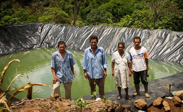 Pedro Ramos, Víctor de León, Ofelia Chávez y Daniel Santos (de izquierda a derecha), ante uno de los dos reservorios de agua de lluvia construidos en su caserío, La Colmena, en el municipio salvadoreño de Candelaria de la Frontera. El estanque es parte de los beneficios de un proyecto de adaptación al cambio climático, ejecutado por la FAO. Crédito: Edgardo Ayala/IPS