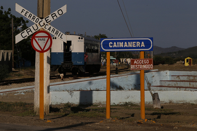 Un tren de un solo vagón transita por la vía en Caimanera, al lado de un cartel que advierte sobre el acceso restringido a esta localidad colindante con la base naval que mantiene Estados Unidos en la bahía de Guantánamo, en el sureste de Cuba. Crédito: Jorge Luis Baños/IPS