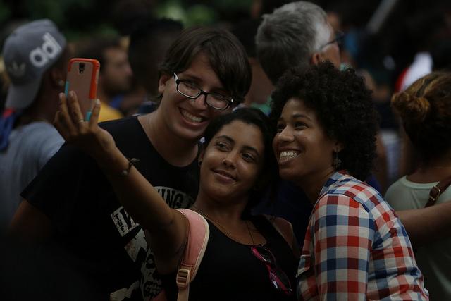 Tres mujeres jóvenes, de rasgos mestizos, se toman una foto durante un acto cultural el espacio expositivo del Pabellón Cuba, en el municipio de Vedado, en La Habana. Crédito: Jorge Luis Baños/IPS