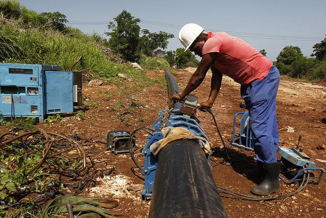 Alexander Concepción Molina, trabajador de la empresa Aguas de La Habana, supervisa el proceso de termofusión de una tubería de polietileno de alta densidad, que es parte de la instalación de las nuevas redes para el suministro de agua potable, en el barrio de Peñas altas, en La Playa Guanabo, uno de los municipios que conforman la capital cubana. Crédito: Jorge Luis Baños/IPS
