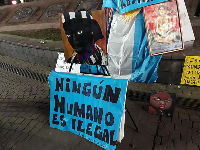 """""""Ningún humano es ilegal"""", rezaba una pancarta con la bandera argentina de fondo, en la protesta contra la violencia de la policía a los vendedores callejeros senegaleses, el 16 de junio frente al Obelisco de Buenos Aires. Casi no participaron senegaleses, aparentemente por miedo a la represión policial. Crédito: Daniel Gutman/IPS"""