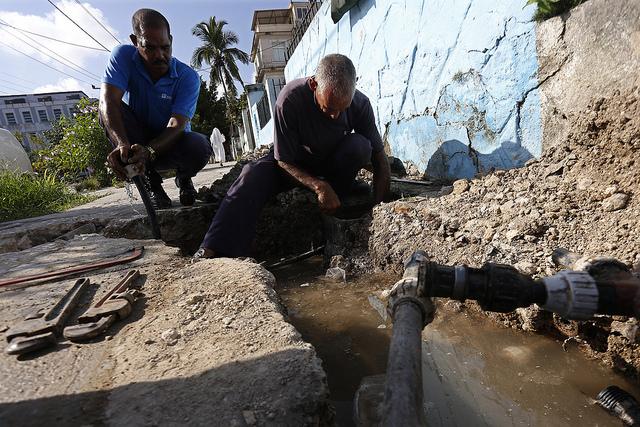 Dos trabajadores de la empresa Aguas de La Habana laboran en la sustitución de las redes hidráulicas y la instalación de metro-contadores en viviendas para medir el consumo de agua potable en una céntrica calle del barrio de Vedado, en el municipio Plaza de La Revolución, en la capital de Cuba. Crédito: Jorge Luis Baños/IPS