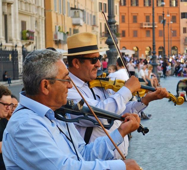 Dos músicos callejeros inmigranters tocan en la famosa plaza Piazza Navona, en Rome. Crédito: Maged Srour/IPS.