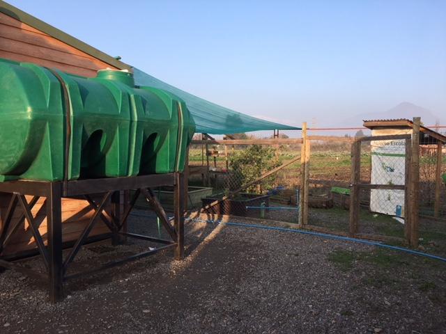 Un tanque con agua de lluvia captada en la escuela Elías Sánchez, en el municipio de Champa, 40 kilómetros al sur de Santiago, que los alumnos usan para regar el contiguo vivero donde cultivan verduras, que instalaron al lado. Su ahorro hídrico mejora las napas que abastecen de agua a la población local. Crédito: Orlando Milesi/IPS