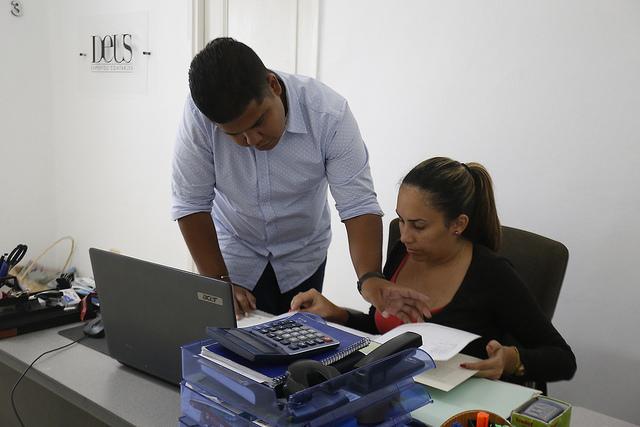 El contador Oniel Santana y la vendedora María Karla Valdés, de la privada empresa DEUS Expertos Contables, que ofrece servicios de consultoría de contabilidad, en una oficina ubicada en el barrio de Miramar, en la capital de Cuba. Crédito: Jorge Luis Baños/IPS