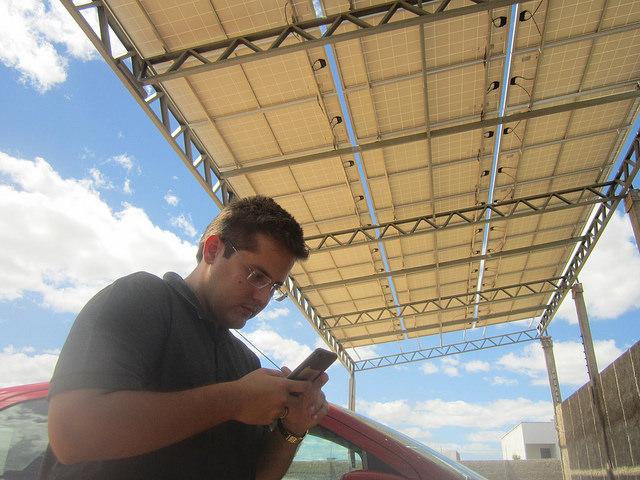 El empresario Paulo Gadelha debajo del techo de placas fotovoltaicas que cubre la zona del aparcamiento para camiones de su matadero de aves. Con la energía solar Gadelha redujo a cero los gastos de electricidad en ese matadero, una planta láctea, una tienda y la vivienda de su familia, en el municipio brasileño de Sousa, en el noreste del país. Crédito: Mario Osava/IPS