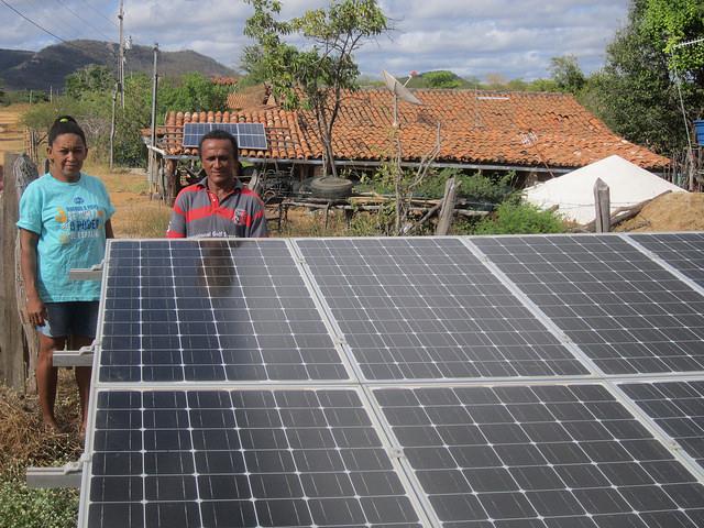 Marlene y Genival Lopes dos Santos, un matrimonio de campesinos, junto a las placas solares de generación compartida, que reducen su cuenta de electricidad luz y las de sus socios urbanos, que viven en las ciudades de Sousa y João Pessoa, capital del estado de Paraiba, distantes 400 kilómetros, en la región del Nordeste de Brasil. Crédito: Mario Osava/IPS