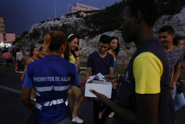 Una pareja de promotores de salud reparten preservativos a un grupo de adolescentes en la entrada de un concierto en el barrio del Vedado, en La Habana, la capital cubana. Crédito: Jorge Luis Baños/IPS