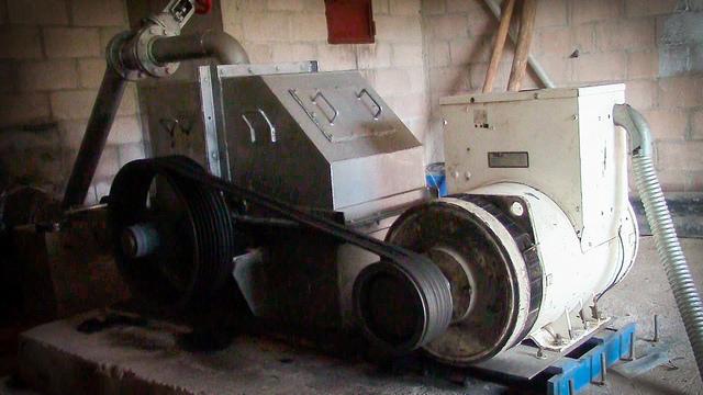 El pequeño generador, en la sala de máquinas construida por los vecinos de Joya de Talchiga. Los hombres del caserío cargaron, con maderos en sus hombros, la pesada turbina que mueve el generador de 58 kW, ya que no hay acceso a vehículos donde se instaló la maquinaria de la Minicentral Hidroeléctrica El Calambre, en el montañoso municipio de Parquín, en el este de El Salvador. Crédito: Edgardo Ayala/IPS