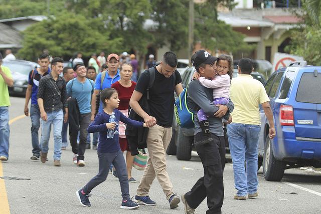 """Sin importar el riesgo o las amenazas, padres e hijos huyen de su país, Honduras, donde la """"fantasía"""" no existe, como este grupo en la aduana de Agua Caliente, en la frontera con Guatemala, donde el gobierno clausuró el paso entre el 19 y el 24 de octubre, en un afán fallido por contener el éxodo. Pero el boquete humano abierto en el país es difícil de cerrar, según expertos. Crédito: Thelma Mejía/IPS"""