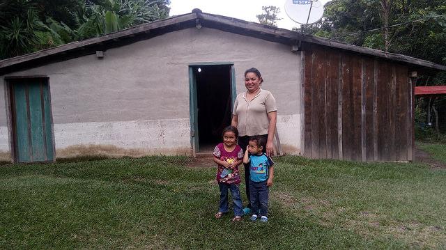 Carolina Martínez, acompañada de sus hijos, delante de su casa, donde se vislumbra un bombillo encendido, en el caserío de Joya de Talchiga, del municipio de Perquín, en el oriental departamento de Morazán, en El Salvador. Esta maestra de 36 años es una de las beneficiarias del proyecto hidroeléctrico comunitario que desde 2012 brinda electricidad a más de 40 familias del lugar. Crédito: Edgardo Ayala/IPS