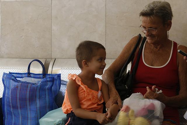 Suelen Suárez, de tres años, y su abuela Milagros Miranda, residentes en un municipio cercano a La Habana, mientras dialogan con IPS en un corredor del Instituto Nacional de Oncología y Radiobiología de El Vedado, en la capital cubana, donde la niña es tratada de un tumor. Crédito: Jorge Luis Baños/IPS
