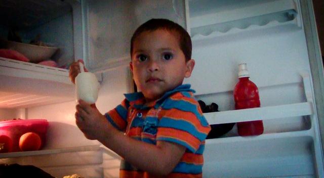 Un niño de La Joya, un caserío del este de El Salvador, mientras toma una charamusca, un helado a base de frutas, del refrigerador de Lilian Gómez, que gracias a la llegada de la electricidad ha montado un pequeño negocio de elaboración de estos productos, ya populares entre sus vecinos. Crédito: Edgardo Ayala/IPS