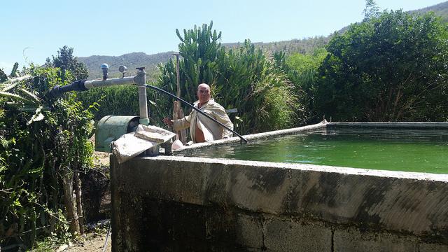 El agricultor Marciano Calamato junto al pozo y la cisterna de que dispone en su finca, para garantizar el riego de sus cultivos al menos una vez al día, en la única zona semidesértica de Cuba, en San Antonio del Sur, un municipio del sureste cubano. Crédito: Ivet González/IPS