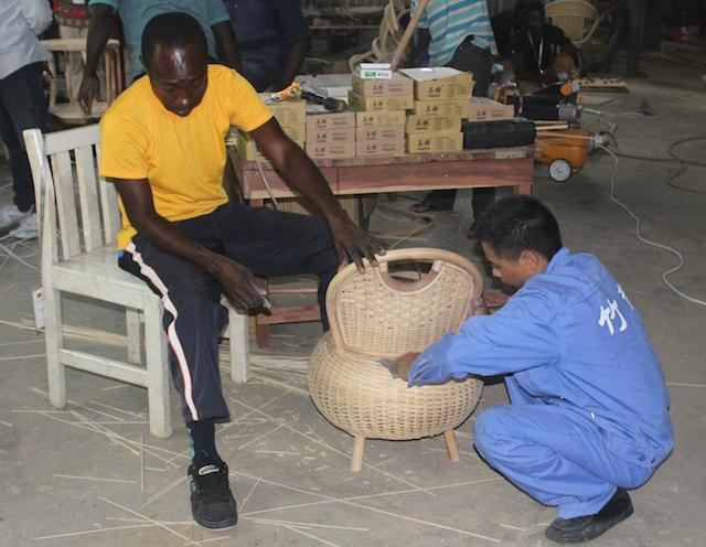 Yaw Owiredu Mintah le da los toques finales a una silla de bambú y ratán, asesorado por su profesor. Crédito: Jamila Akweley Okertchiri/IPS.