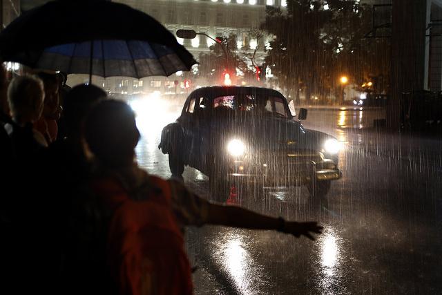 Durante una noche lluviosa, varias personas intentan detener un viejo vehículo que opera como taxi privado, en una céntrica calle de La Habana Vieja, en la capital de Cuba. Crédito: Jorge Luis Baños/IPS