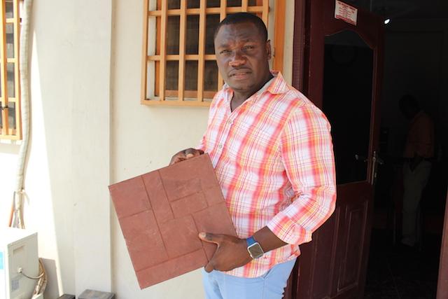 Nelson Boateng, director ejecutivo de Nelplast Ghana Limited, es uno de las muchas personas y empresas que buscan usos alternativos para la basura plástica. En la foto sostiene una baldosa hecha de materiales reciclados.. Crédito: Albert Oppong-Ansah/IPS.