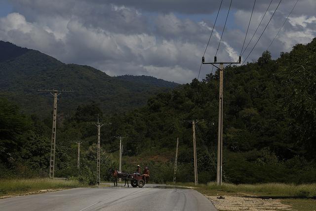 Dos hombres transitan por una carretera en una carreta tirada por un caballo en un área rural del municipio montañoso de Guamá, en el este de Cuba. Crédito: Jorge Luis Baños/IPS