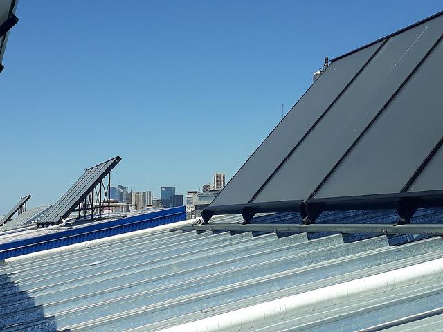 Algunos de los paneles solares instalados en los techos del complejo residencial de La Containera, en la Villa 31, y de fondo las torres del área de lujosas oficinas de la capital argentina. El asentamiento precario tiene una ubicación privilegiada dentro de Buenos Aires, al lado de La Recoleta, uno de sus barrios más cotizados. Crédito: Daniel Gutman/IPS