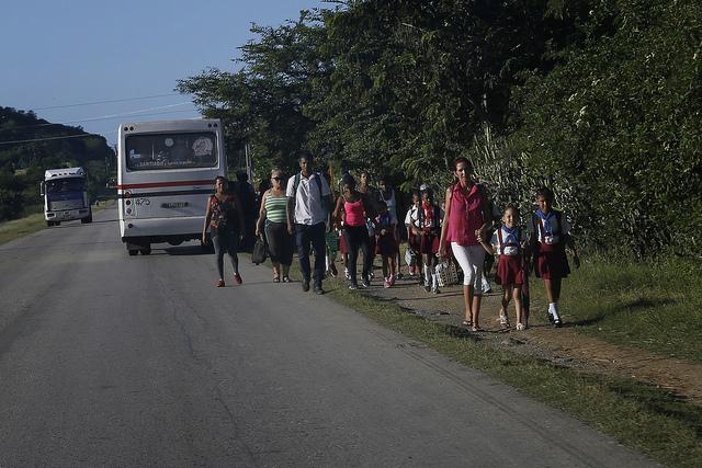 Un grupo de personas, mayoritariamente mujeres y niños, camina al borde de una carretera que sirve de vía de comunicación, en el municipio de Palma Soriano, en la oriental provincia de Santiago de Cuba. Crédito: Jorge Luis Baños/IPS