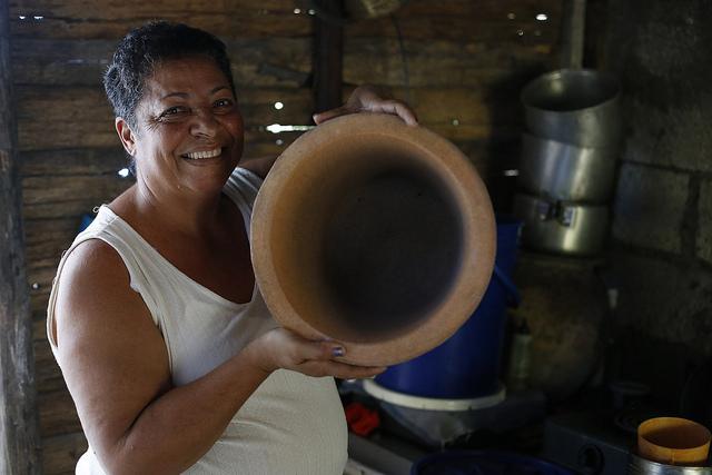 Maritza Milán, de 59 años, quien se dedica a la atención de su hogar y su familia, muestra un filtro artesanal empleado en la purificación del agua, en su humilde casa de madera, en el barrio de El Congrí, en la periferia de la ciudad de Palma Soriano, en el este de Cuba. Crédito: Jorge Luis Baños/IPS