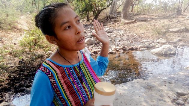 Silvia Ramírez muestra cómo ha disminuido el caudal de riachuelos que circundan el caserío San Fernando, en el este de El Salvador, debido entre otras razones al uso excesivo de agua por parte de los productores de caña, que embalsan sus cauces en pequeñas represas para luego desviar el agua a sus cultivos, afectando a las comunidades rurales del entorno. Crédito: Cortesía de Edgardo Ayala